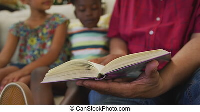 Mid section of grandfather and grandchildren reading book at...