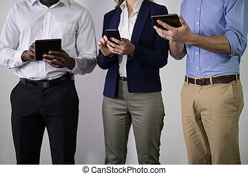 Mid section of male and female executives using electric gadgets