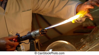 Mid section of male worker creating glass in glass factory ...