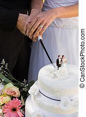 Mid section of newlywed cutting wedding cake