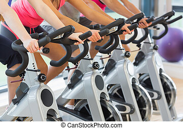 Mid section of people working out at spinning class - Mid ...