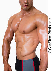 Mid section of shirtless muscular man posing over white...