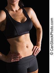 Mid section of slender fit woman posing in sportswear on...