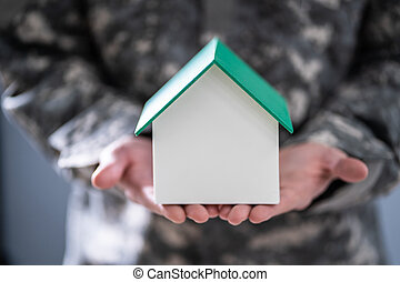 Soldier Holding Model House In Hand