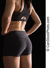 Mid section of the backside of young slim woman wearing sportswear on black background