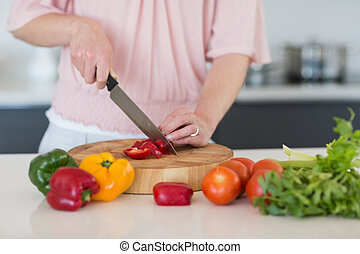 Mid section of woman chopping vegetables