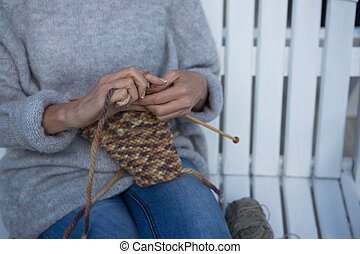 Mid section of woman knitting wool