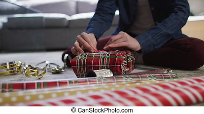 Mid section of Caucasian woman at home at Christmas, sitting on floor in living room wrapping present, tying ribbon, slow motion. Social distancing during Covid 19 Coronavirus quarantine lockdown.