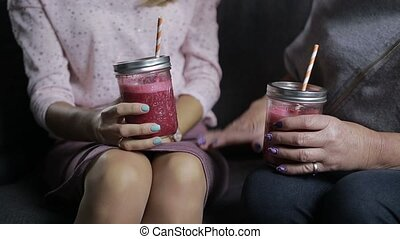Mid section of women with smoothie jars talking - Mid...