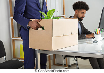 Businessperson Packing Belongings In Cardboard Box