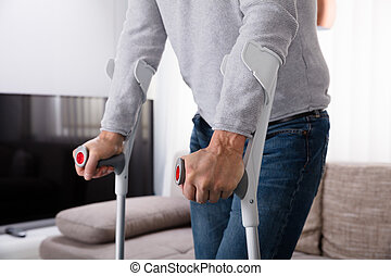 Man With Broken Leg Using Crutches