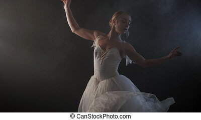 Mid Shot of a Beautiful Young Ballerina Spinning Gracefully in the Spotlight. She dressed in white airy dress modern tutu. Sensual woman on smoke black stage. Slow motion.