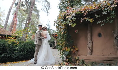 Mid view of young groom in suit hugging his beloved bride in luxurious dress next to cozy country houses, covered with leaves and located in the forest. European wedding couple walks in autumn park.