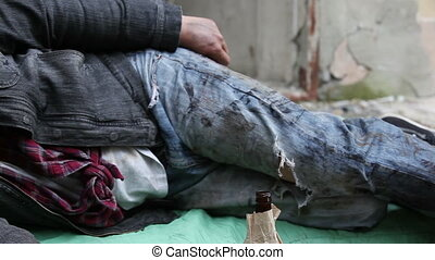 Man in ragged clothes sleeping with a bottle of beer nearby