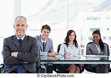 middelbare leeftijd , het glimlachen, directeur, zittende , met, zijn, gekruiste wapens, en, met, zijn, team, achter, hem