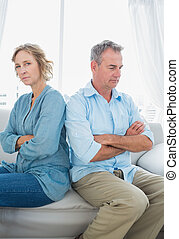 middelbare leeftijd , paar, zitting op de bank, niet spreken, na, een, vechten, met, kijkende vrouw, aan fototoestel, thuis, in, de, woonkamer