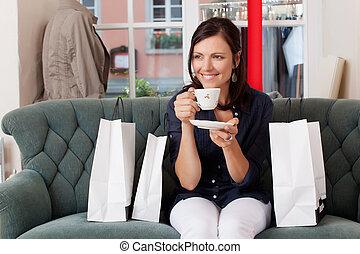 midden volwassene, vrouwlijk, klant, drinkende koffie, terwijl, zitten op sofa, op, de opslag van de kleding
