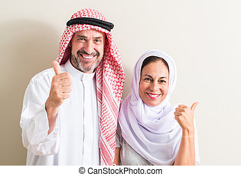 Middle age arabic couple, woman and man happy with big smile doing ok sign, thumb up with fingers, excellent sign