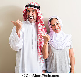 Middle age arabic couple, woman and man pointing with hand and finger up with happy face smiling