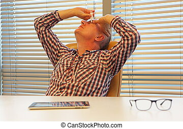 middle age caucasian man applying eye drops sitting at the desk in office