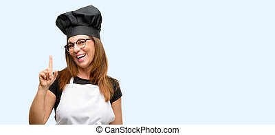 Middle age cook woman wearing chef apron pointing away side with finger