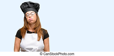 Middle age cook woman wearing chef apron with sleepy expression, being overworked and tired