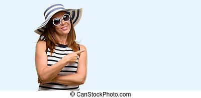 Middle age cool woman wearing summer hat and sunglasses pointing away side with finger