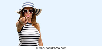 Middle age cool woman wearing summer hat and sunglasses pointing to the front with finger