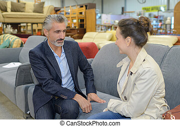 middle age couple buying sofa in furniture store