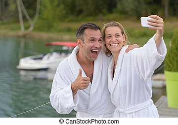 middle-age couple on lake makes a selfie
