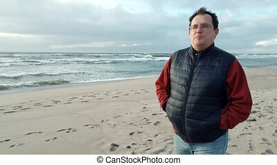 Middle age man alone walking at sea shore