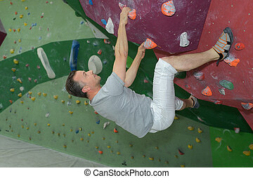 middle-age man climber on artificial climbing wall