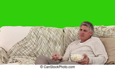Middle-age man eating popcorn while he is watching tv