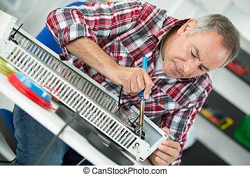 middle-age man plumber fixing radiator