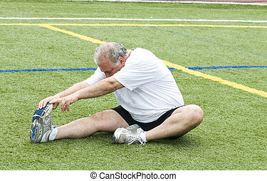 middle age man stretching and exercising on sports field - ...