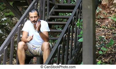 middle age man talking smartphone - middle age brunette man...