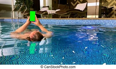 Middle age man using smartphone in the pool at spa zone in...
