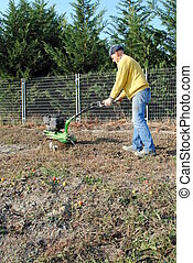 Middle age man with a rototiller in the garden
