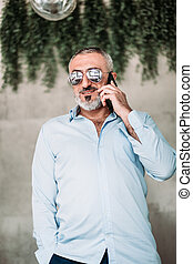 Middle age man with beard and with sunglasses talking on the phone.