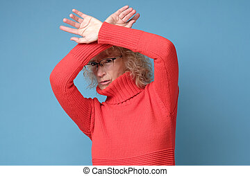 Middle age mature woman wearing red sweater and glasses doing stop gesture
