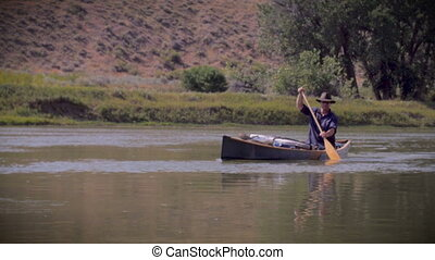 Middle age outdoorsman paddles a blue canoe down a river - A...