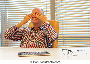 middle age practicing yoga for eyes in office - having break...