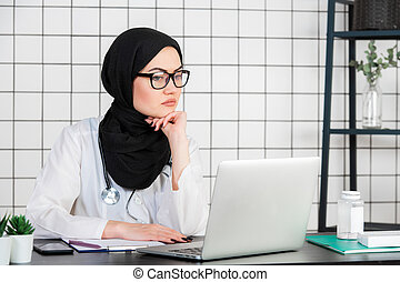 Middle age senior arab nurse woman wearing hijab at medical office with hand on chin thinking about question, pensive expression. Doubt concept.