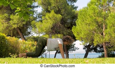 Middle age woman doing yoga on green grass. Sportive woman...
