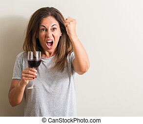 Middle age woman drinking red wine in a glass annoyed and frustrated shouting with anger, crazy and yelling with raised hand, anger concept