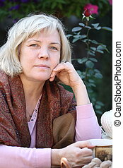 Middle age woman drinking tea in the garden