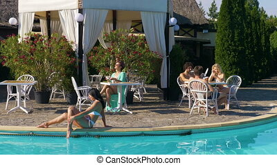 Middle age woman drinks a coffee at a table and young woman sits by the pool while a group of teenagers is chatting at another table