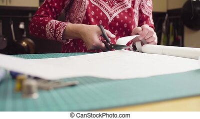 Middle-age woman hands with scissors cutting paper pattern....