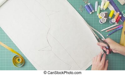 Middle-age woman hands with scissors cutting paper template....