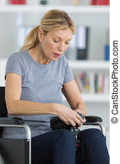 middle-age woman on a wheelchair looking image in the camera